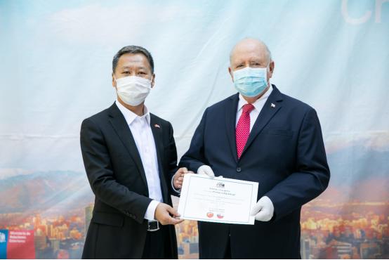智利驻华大使路易斯·施密特(右)与京东集团副总裁龙宝正(左)出席物资施舍交接仪式