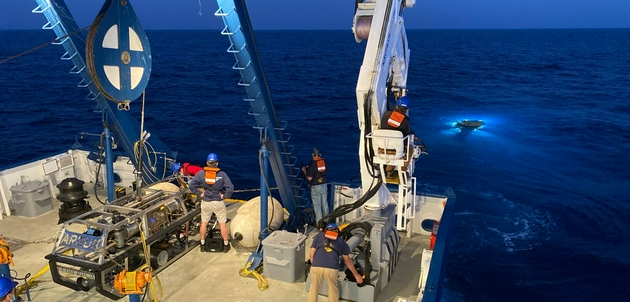 大力神号远程操控潜水器(ROV)在黑暗的太平洋深水区域缓慢下降,它将用于搜寻一种治疗脑癌的海洋微生物