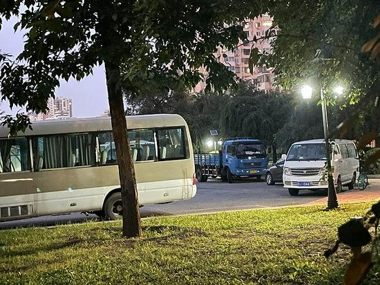 对外经济贸易的校道内停着多辆卡车、客车等。