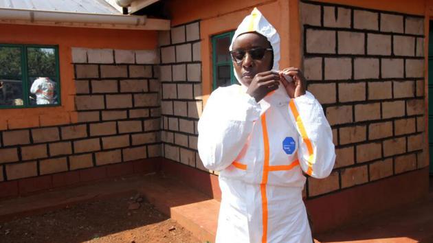米莉森特·米纳约和同事在村庄采集样品时必须穿上全套防护服