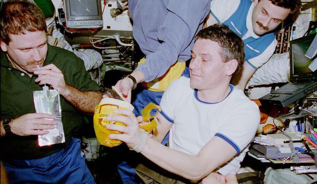 2、这是和平号空间站的用餐时间,在这张1997年的照片中,美国宇航员杰夫•格伦斯菲尔德(左)正在喝饮料,而宇航员瓦莱丽•科尔森、亚历山大•卡雷利在一旁看着。