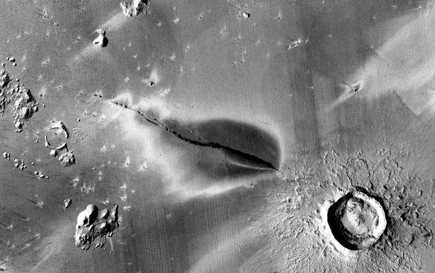 在科柏洛斯槽沟地区,延伸到裂缝两侧的黑色斑点标志着火星近期存在火山活动。直径约13公里。图片来源:NASA/JPL/MSSS/The Murray Lab。