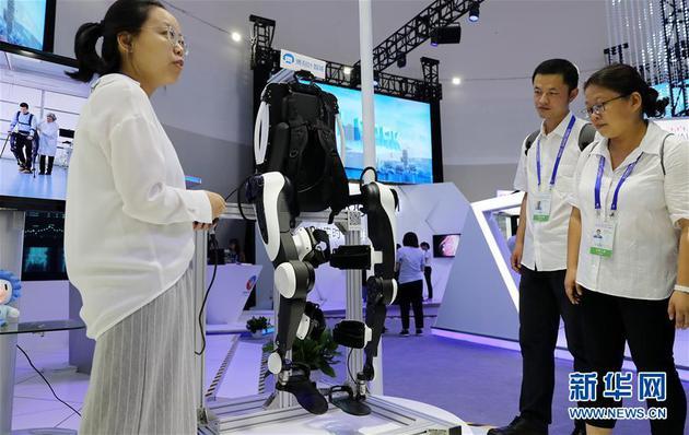 9月17日,工作人员(左)在大会现场向参观者介绍一款外骨骼机器人。新华社记者 方喆 摄