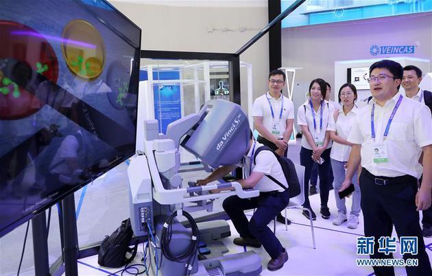 9月17日,参观者在大会现场观看一个机器人手术系统的作业演示。新华社记者 方喆 摄
