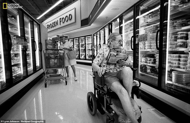 """她被描述为""""性格棱角显明,愤世嫉俗,未必有点恶巴巴的,但也很慷慨时兴、关心他人。""""图为苏珊正坐着轮椅逛超市,轮椅上贴了一张写着""""天佑美利坚""""的贴纸。她在二战后从德国侨民到了美国。"""