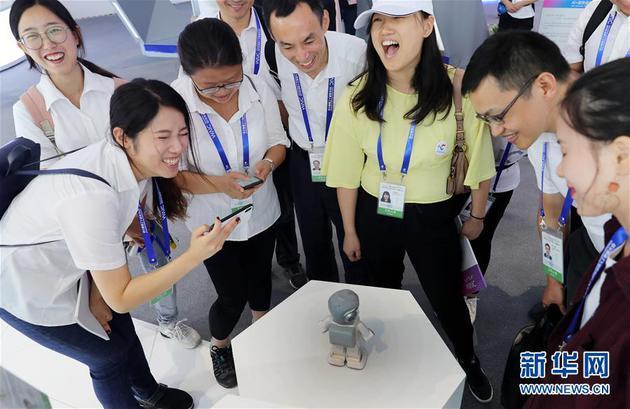 """9月17日,在大会现场,一个名叫""""悟空""""的家庭陪伴型智能机器人引得参观者大笑。新华社记者 方喆 摄"""