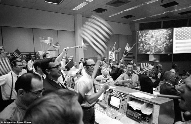 在这张1969年7月24日的照片中,飞行控制人员在休斯顿载人航天中心任务控制中心的任务操作控制室里,庆祝阿波罗11号登月任务的成功完成
