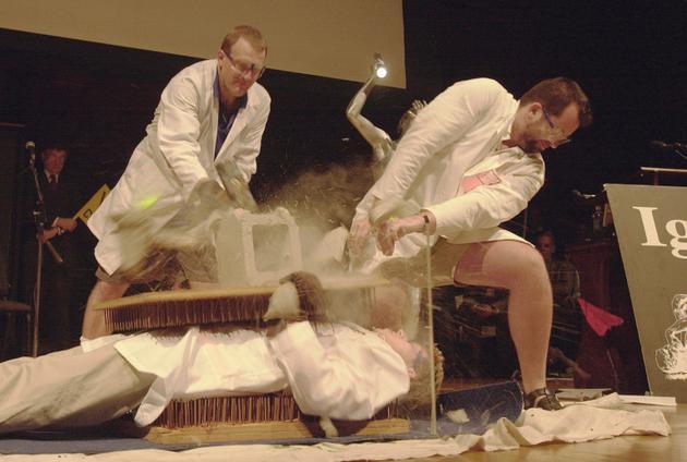 """哈佛大学讲师丹尼尔·罗森伯格(左)在2001年搞笑诺贝尔奖颁奖典礼上对同事尼尔斯·索伦森进行""""胸口碎大石"""",后者当时躺在钉床上"""