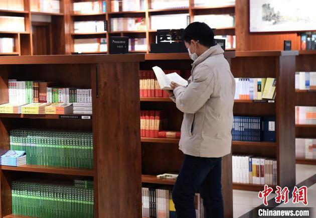 资料图:图为重庆书城恢复营业,市民戴着口罩翻阅图书。周毅 摄