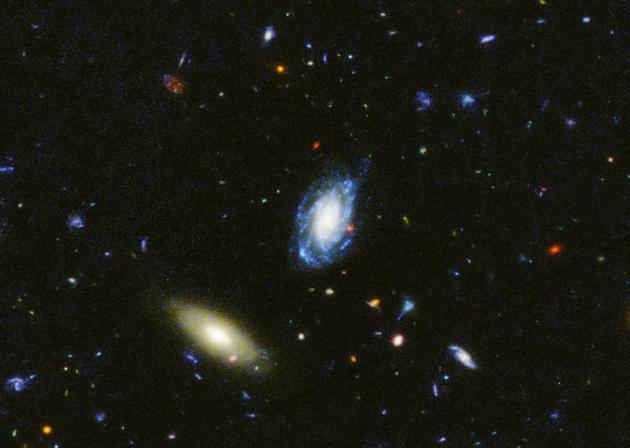 """在""""大天文台宇宙起源深空巡天计划南天区""""(GOODS-South field)的紫外光图像中可以看两个邻近宇宙的星系,其中一个正在活跃地形成新恒星(蓝色),另一个则只是普通星系。在背景中,可以看到遥远的星系及其星族。根据星系内部恒星的年龄,以及已测量到的星系距离,我们可以确定它们内部的恒星是何时形成的。"""