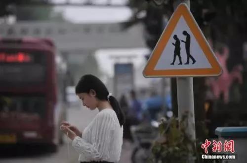 """材料图:重庆一红绿灯处摆放""""不做抬头族、存眷红绿灯""""警示牌。 陈超 摄"""