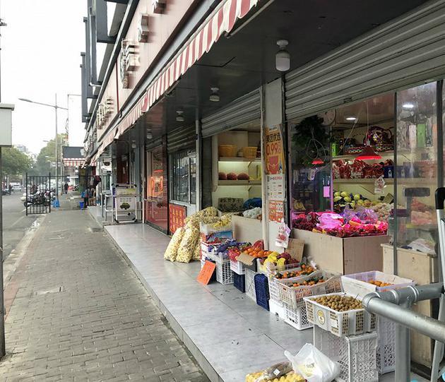 三元二村菜市场门口的水果店已经成为社区团购的自提点之一。摄影:佘晓晨