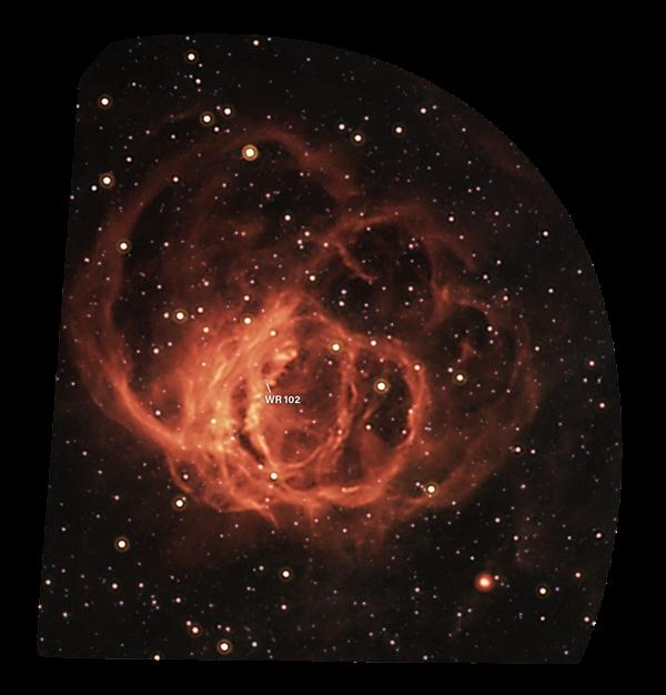 WR 102隐藏在这红外图像拍摄到的星云状物中心。恒星的极端辐射正在电离周围气体,从而使气体发光。