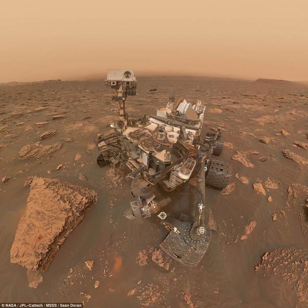 """即使在沙尘暴肆虐的情况下,好奇号仍在盖尔撞击坑拍下了这张""""自拍照"""",并将其传回了地球。但远处的群山和岩石已经被厚厚的沙尘所覆盖,看不清真容。"""