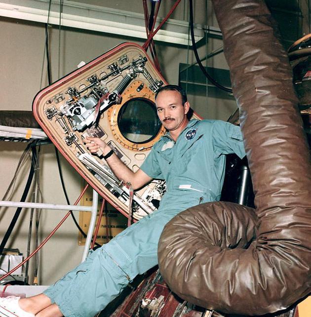 在月球物质回收和回归宇航员检疫实验所接受了详细检查后,迈克尔·柯林斯坐在阿波罗11号指挥舱的舱口