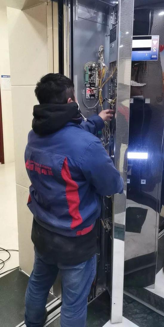 湖北宜昌的做事人员正在安置电梯声控设备。