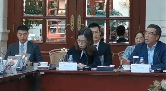 梁华(前排右)在座谈会上。视频截图