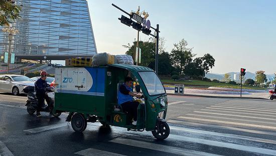 双11期间桐庐街头的快递幼哥。(拍摄:杨霞)