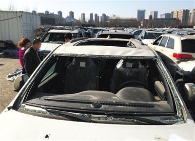 """25日,天津""""中电物流""""停车场,购车者正在参观天津港爆炸受损车辆。"""