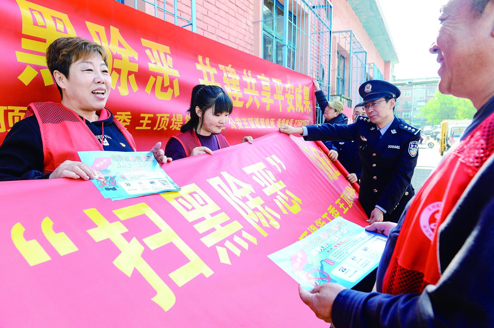 民警和志愿者懸掛掃黑除惡宣傳橫幅