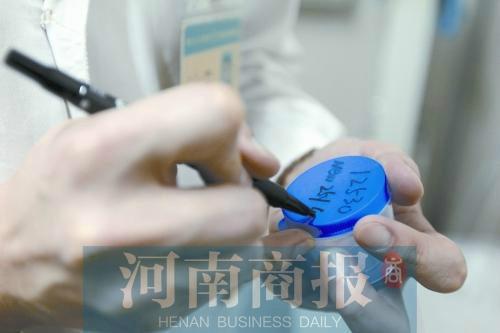 工作人員在取精杯上編寫序號后交給捐精者(資料圖)