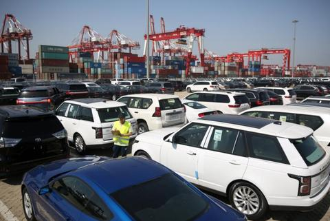 山东青岛港口工作人员为进口车登记(图源:路透社)