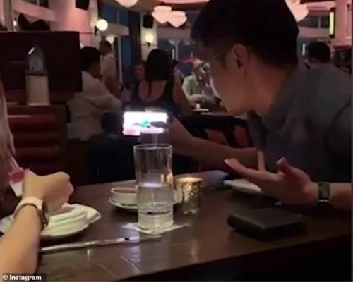 图为亚洲夫妇观看折纸视频。(图:《每日邮报?#32602;? style=