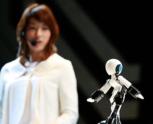 """日本机器人展览上,机器人在表演""""模特步""""。新华社记者任正来摄"""