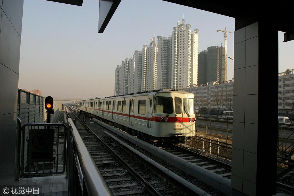 2003年12月27日,北京地铁八通线正式全线通车运营。列车驶过珠江绿洲楼群,八通线的开通带动北京东部沿线楼盘升温。图片来源:视觉中国