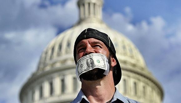 2013年10月1日,美国华盛顿,别名嘴上贴着美元纸钞的外子呼吁国会议决预算案。图片来源:视觉中国