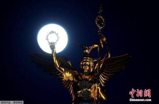 资料图:德国柏林,月亮与胜利纪念碑顶端的金色维多利亚相映成趣。