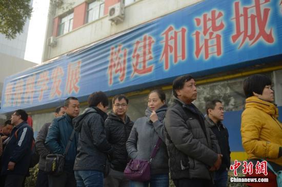 """11月19日,山西太原劳动力市场开放""""4050""""公益岗位招聘,千余名年龄在40岁至50岁的下岗职工排着长队求职。中新社发 韦亮 摄"""