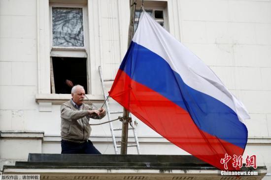 当地时间2018年3月14日,一名男子将俄罗斯驻英国大使馆门前的俄罗斯国旗取下。