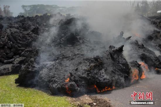 图为阻断道路的熔岩仍在不断燃烧。