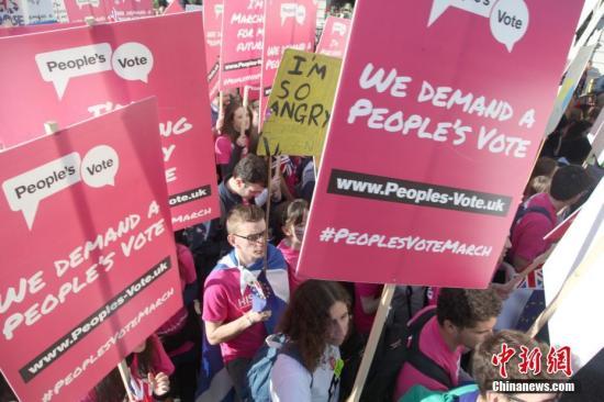 """资料图:2018年10月20日,67万英国民众汇集在伦敦议会广场举行示威游行活动,呼吁对英国脱欧最终协议举行全民投票。图为示威游行人群高举标语牌,呼吁举行""""人民投票""""。中新社记者 张平 摄"""