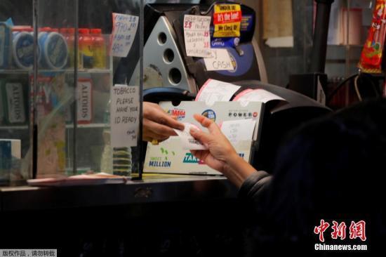 彩民从店员手中接过购买的彩票。