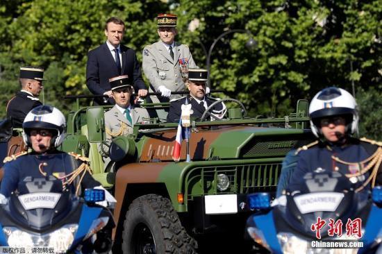 原料图:法国总统马克龙检阅士兵。