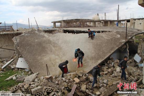 资料图:当地时间2019年1月30日,叙利亚伊德利卜Jisr al-Shughur,当地一学校遭炮击,学生在受损的教室和操场学习和玩乐。