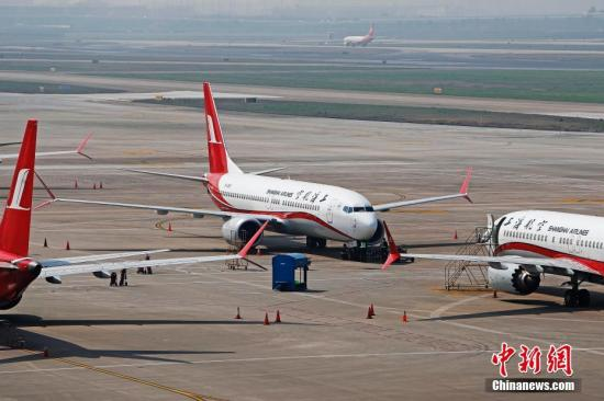 资料图:3月17日,上海航空公司的9架波音737MAX机型飞机停在虹桥国际机场停机坪上,工作人员正在对飞机进行检查。据路透社报道,波音公司计划将在未来一周到10天内发布波音737MAX机型相关升级软件。目前,波音737MAX机型已经在全球停飞。中新社记者 殷立勤 摄