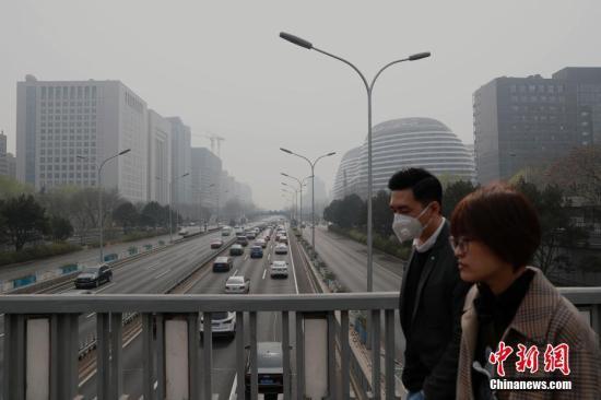 资料图:市民戴口罩出行。中新社记者 刘关关 摄
