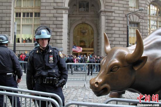 """资料图:2011年,""""占领华尔街""""示威者途径华尔街著名标志铜牛雕塑,防暴警察在那里守卫。中新社发 李洋 摄"""