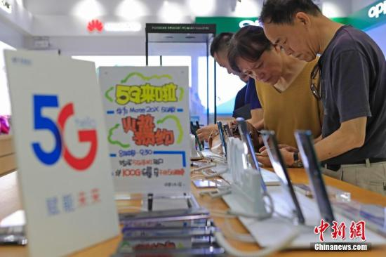 Data map: People handle 5G mobile phone and network related services. Photo by Yin Liqin