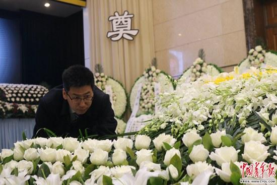 告別儀式開始前,靳中學在整理逝者遺體身旁的鮮花。