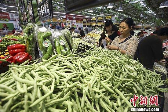图为民多在山西太原一超市选购蔬菜。 中新社记者 张云 摄