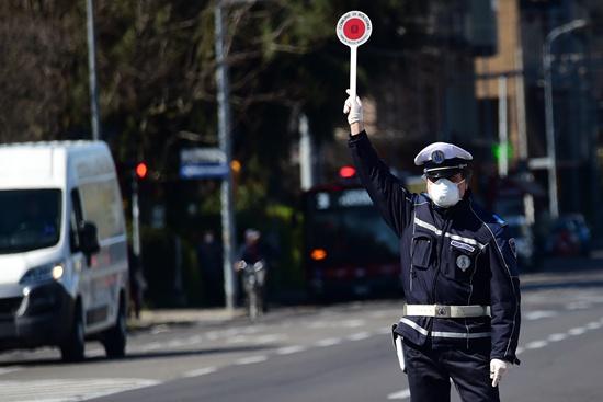"""3月23日,在意大利博洛尼亚,警察拦下过往车辆准备检查人们出行的""""自我声明""""。詹尼·斯基基/摄(新华社发)"""