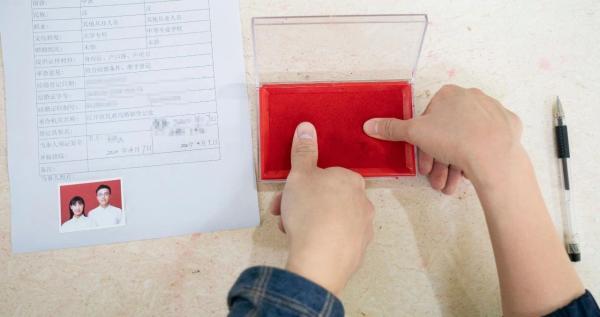 4月7日,在武汉市江岸区民政局婚姻登记处,新秀办理结婚手续时按手印。新华社记者 才扬/摄