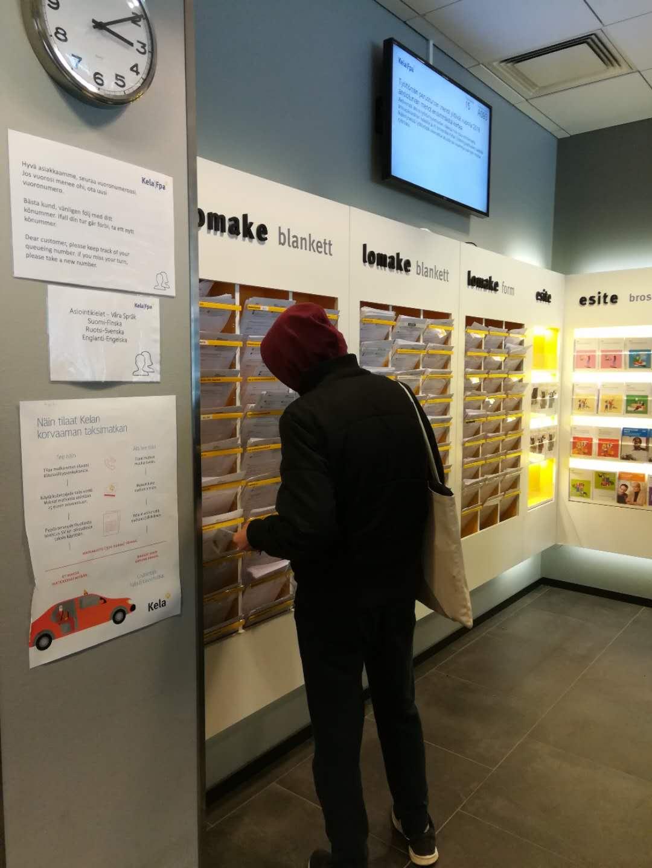 芬兰国民社保局内,一名申请补贴者正从种类繁多的申请表中找自己需要的材料。 张蕾摄