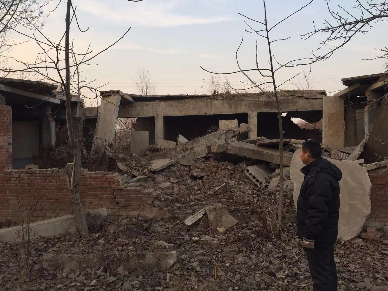 12月4日,养猪户李树军站在被清除的房屋前。新京报记者赵凯迪摄