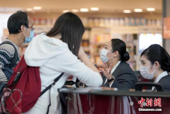 资料图:香港国际机场的工作人员戴口罩接受旅客问询。中新社记者 张炜 摄