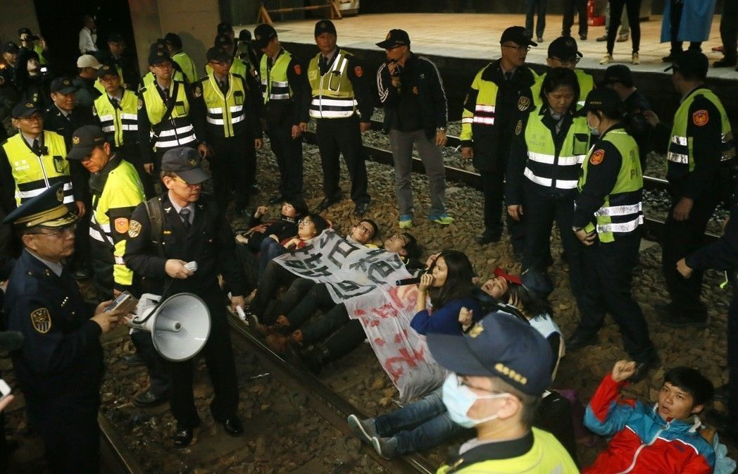 """劳团到北车卧轨抗议""""劳基法""""修恶,遭大批警力逮捕。(图片来源:台湾《联合报》)"""